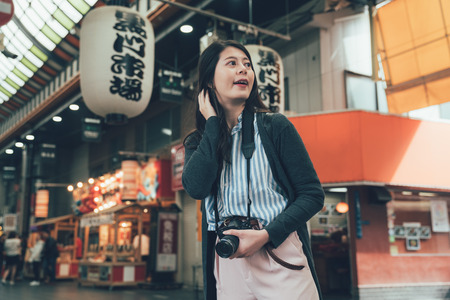 vintage photo of happy excited emotional young woman photographer tourist with camera standing in entrance of japanese local market in osaka japan. Translation on lantern text kuromon ichiba market. Zdjęcie Seryjne