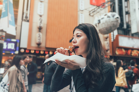 Asian young female model eating octopus ball dumpling on teeming dotonbori area osaka japan. local lady eating street food takoyaki with cheerful smiling face. huge puffer fish balloon in back