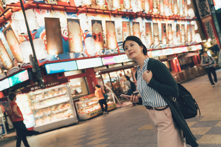 vintage style of beautiful asian woman outdoors at night using mobile phone searching online map walking on urban street. young girl traveler pass by famous seafood restaurant dotonbori osaka japan.