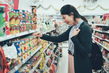 sale shopping consumerism people concept. asian woman backpacker with curious face picking snack cookies choose at grocery supermarket. lady buying products food instant noodles in convenience store. Stock fotó - 118116127