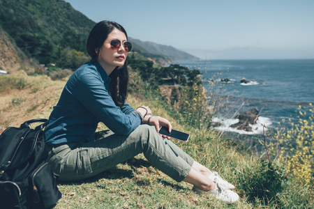 beautiful lady holding mobile phone sitting on meadow and looking at blue ocean view.