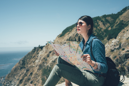 female chinese hiker with backpack sit on top of the mountain holding map. Stok Fotoğraf