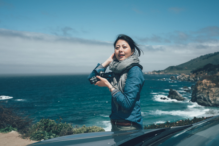 travel asian woman photographer holding professional camera at the California State Route Highway 1 along the pacific ocean.