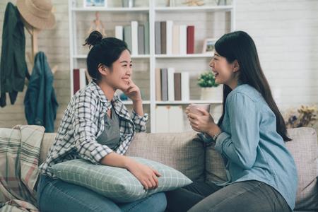 Deux femmes asiatiques décontractées se reposant sur un canapé avec une boisson chaude. Banque d'images