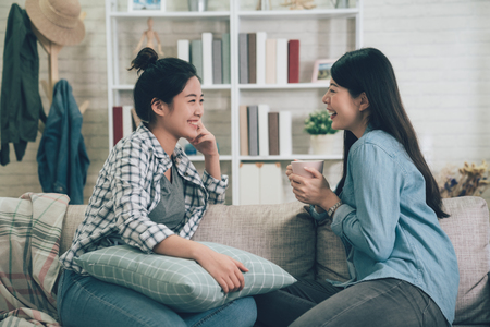 Two asian casual women relaxing on sofa with hot drink. Фото со стока