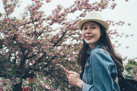 Happy young chinese woman using smartphone on sunny day with cherry flower tree blossom in background. Reklamní fotografie