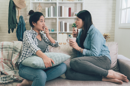 Two asian girls gossiping at home. Banque d'images