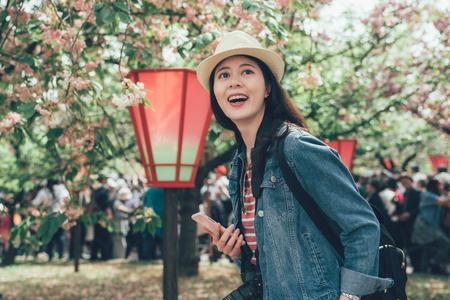 Happy teenage girl tourist in sakura park.