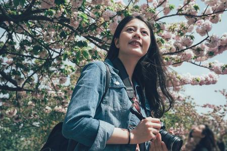 Professional female photo shoot camera outdoor standing under pink cherry sakura flower tree.