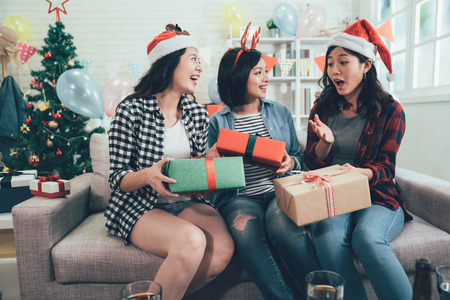 young people celebrating christmas eve at home. three girls exchanging gifts on boxing day with surprised face looking at present. charming asian women in santa hats having fun together.