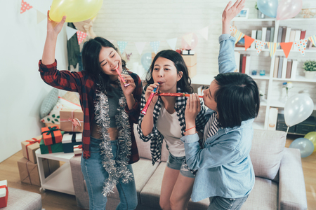 happy female students enjoy house party celebrating graduation playing with blowers. carefree girls dancing raising hands with toys and music in the cozy living room in decorated home. Standard-Bild