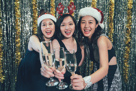 charming asian ladies in santa hats clinking wine glasses face camera smiling attractive. group of young people celebrating christmas at club toasting champagne. cheers people cheerfully with alcohol Stock Photo