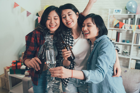 group of happy young asian women holding alcohol drinks hugging together smiling. cheers toasting glasses lifestyle concept. carefree best friends having fun celebrating party at home.
