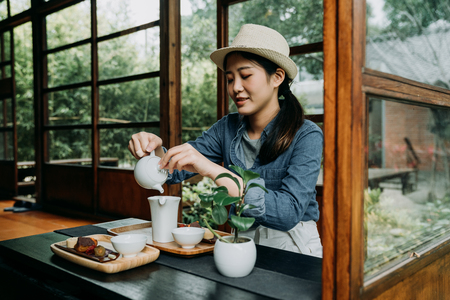 elegant beautiful asian girl doing chadou organic green matcha tea in bowl sitting in japanese wooden house. Banco de Imagens - 118710313