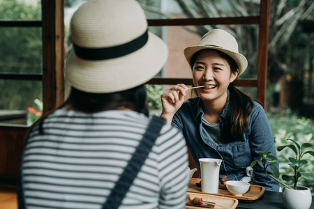 two asian woman traveler in kyoto eating local tasty dessert and talking happily.