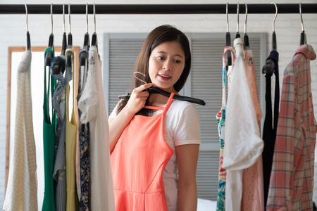 clothing wardrobe fashion, style and people concept. happy asian woman with dress on hanger looking at mirror at home in cozy bedroom. single lady choosing cloth outfit in apartment for date.