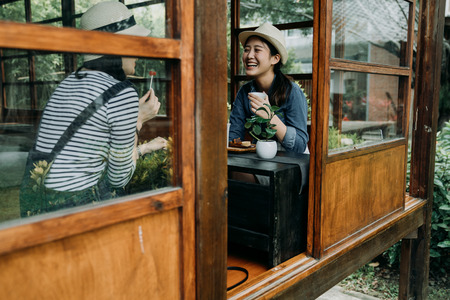 communication and friendship concept. smiling young asian women with tea bowls in chado shop outdoor cafe. girl best friends laughing chatting talking cheerful relax in japanese old wooden house zen 版權商用圖片 - 123140762
