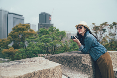 asian female tourist photographer taking picture of osaka japan business area skyscraper tall buildings. independent girl traveling alone recording trip with camera leaning on rock by spring park. Stock Photo