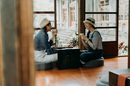 group of best friends sitting wooden old house floor holding matcha tea bowl doing chanoyu. asian woman travel in tokyo lifestyle. laughing young girls talking drinking enjoy in japanese garden
