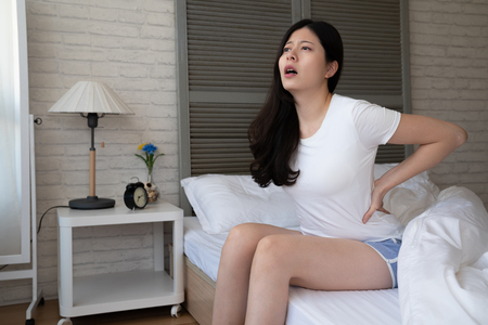 people healthcare and problem concept. unhappy young chinese woman suffering from pain in back reins in bedroom at home. uncomfortable female waist hurting while sit up wake up in morning on bed. 写真素材