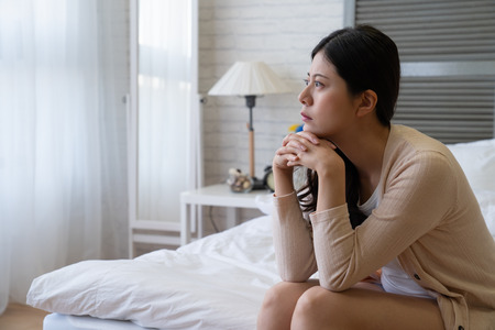 Unsmiling woman looking out window with curtain sitting in cozy bedroom in apartment. thoughtful depressed asian lady looks worried in bed. frustrated girl at home hands cross on chin frowning think Stockfoto - 118961566