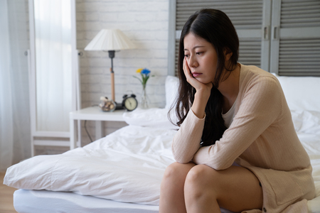 Sad depressed  woman with smock jacket suffering from insomnia sitting in bed. thoughtful girl touching her face sleep disorder and stress concept. asian female resting at home in day time 免版税图像 - 118960373