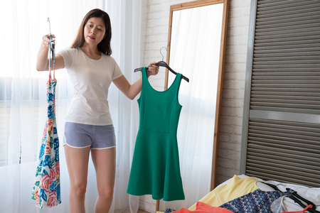 clothing fashion style and people concept. happy asian woman choosing cloth at home wardrobe holding two dresses flora flower colorful or green standing next to mirror in cozy bedroom by window