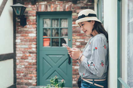 Beautiful teenager student girl using smart phone leaning against plain red stone texture brick wall networking and smiling outdoors. Adolescent technology lifestyle. vintage asian woman happy stand Stock Photo