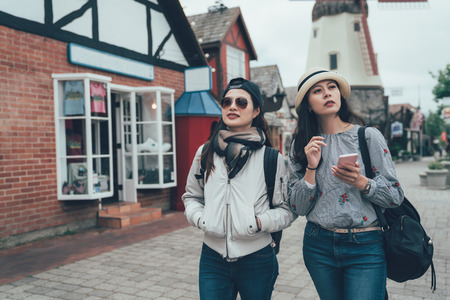 two happy Asian women walking in Copenhagen city street. Denmark spring travel tourist visiting tour finding searching direction of famous attraction by cellphone online map. elegant girls hold phone