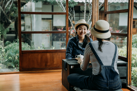 two happy young asian women tourist chatting talking smiling laughing in wooden traditional house in kyoto japan. spring nature garden in background outdoor through window door. friends do chado.
