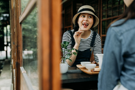 two happy girls spend time together travel osaka japan. Beautiful asian women relaxing enjoy japanese local sweets in traditional wooden house by summer garden. friends drinking matcha tea and snacks Stock Photo - 119515618