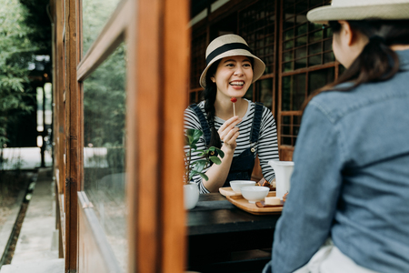 two asian female best friends gathering together on tea ceremony party eating japanese sweets cakes enjoyment happiness. beautiful girls traveler in tokyo lifestyle. summer zen garden teien view. Stock Photo