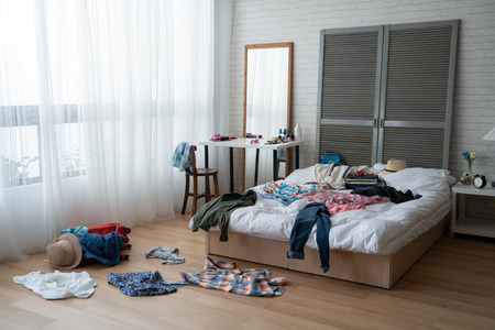 modern bright bedroom with messy clothes scatter on white bed and floor.