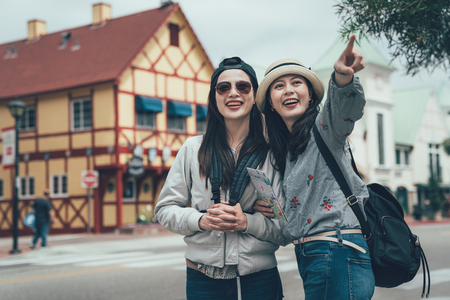 two happy girl friends holding map and pointing finger outdoor in copenhagen denmark.