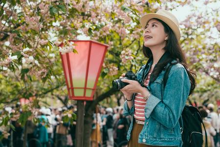 woman photographer take cherry blossom photo at outdoor spring park. Reklamní fotografie