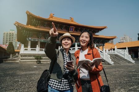 Young asian female tourists holding travel guide book visit temple in beijing. Stock Photo