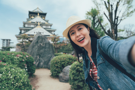 Tourism in japan. happy female tourist take photo selfie in front of osaka castle. asian woman backpacker in straw hat standing in japanese style garden with big rock make self portrait with palace.