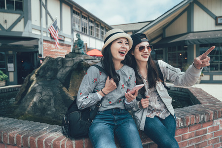 beautiful two asian women traveler with sunglasses and hat laughing cheerfully pointing finger with funny things happen on street sitting by wishing pool. smiling female travel solvang santa barbara
