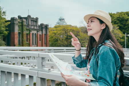 Young tourist asian woman with paper map pointing finger to beautiful top view standing outdoor under sunny day with osaka castle background. girl wear straw hat enjoying vacation in spring travel