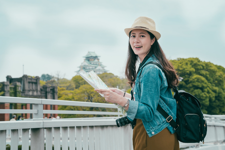 beautiful asian woman enjoying self guided travel outdoor osaka castle in japan. young female backpacker holding paper map standing under bright blue sky carrying digital lens smiling face camera Reklamní fotografie - 119571059