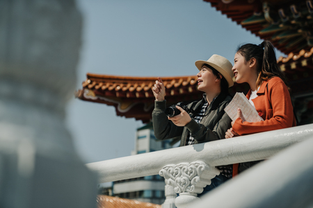 two happy female tourists sightseeing in Beijing Guozijian Confucius Temple china. young asian women travelers leaning relax on railing holding guide book and camera talk. girl showing friend point