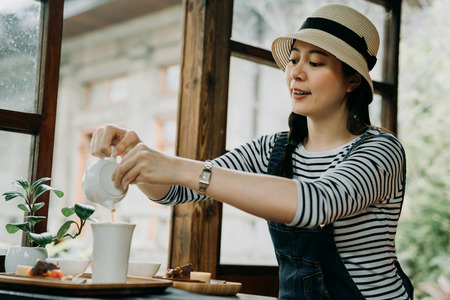 elegant asian woman traveler in straw hat holding teapot pouring tea in bowl sitting in japanese garden house. young girl travel in kyoto japan. chinese lady experience chado ceremony sweets on table
