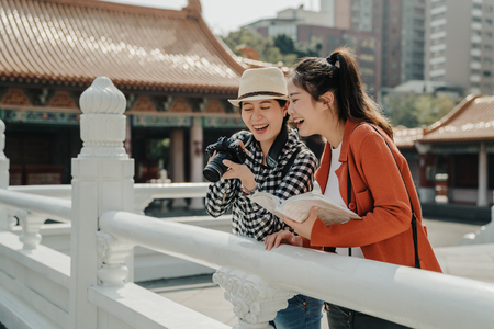 happy young best friends checks photos on camera standing by white marble stone railing in Chinese Temple. Stock Photo