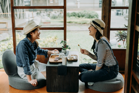 two girlfriends laughing with jokes drinking matcha  having tea ceremony experience. Stock Photo