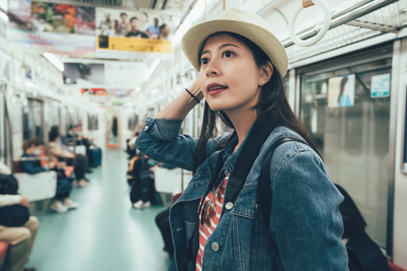 Smiling asian young woman taking journey in public train .