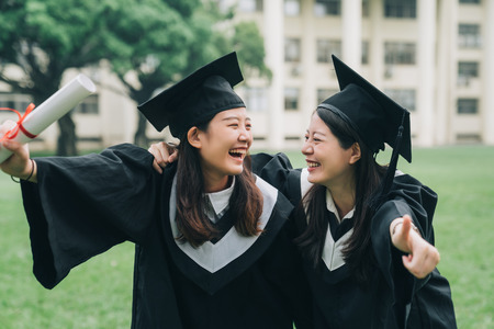cheerful ladies students hugging shoulders arms with thumb up finger and looking each other smiling