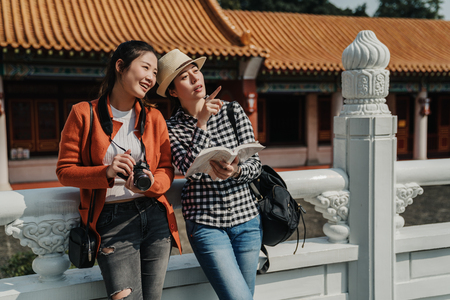 Young asian women travelers holding guide book in hands pointing direction to female photographer friend. girls showing place searching destination outdoor discussing leaning on white marble railings Stock Photo