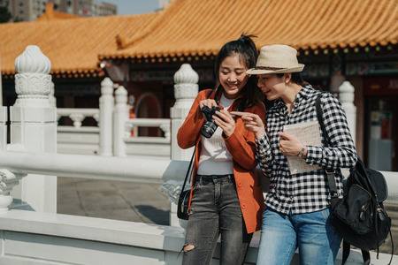 two happy female tourists checking photos on camera leaning on chinese traditional building stone railings. young girl point finger showing friend laughing smiling chatting hold bag and guide book