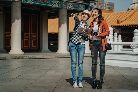 full length of two beautiful asian girlfriends walking on tour trip in beijing china. japanese ladies tourists standing on ground girl showing point finger chinese garden view in confucius temple.