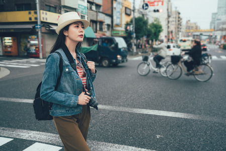 woman pedestrian walking to cross the road outside on sunny day. young elegant female photographer hold professional camera on zebra crossing with cars trucks and bike bicycles in japan osaka city.